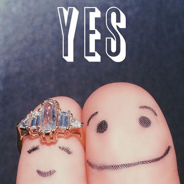 Dedos de una pareja pintados con caras felices diciendo Sí, acepto