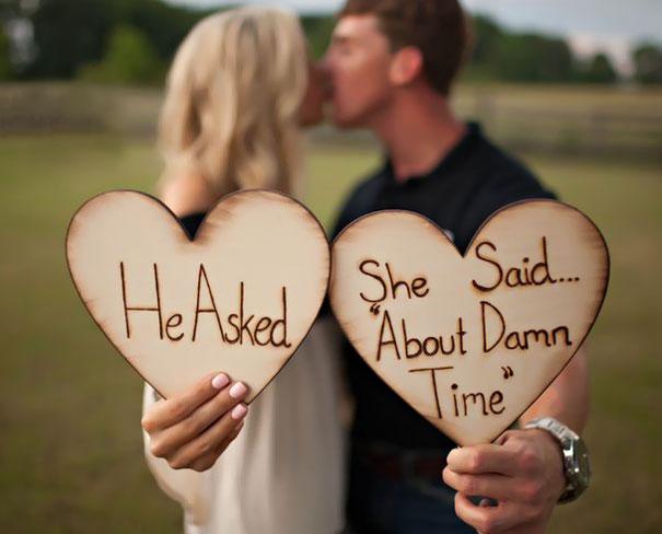 Pareja anunciando su compromiso con corazones hechos de madera