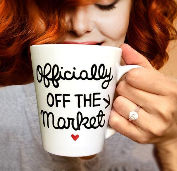 Chica anunciando su compromiso mientras sostiene una taza de café