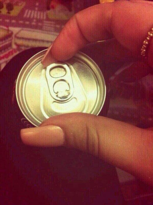 chica con uñas largas abriendo lata