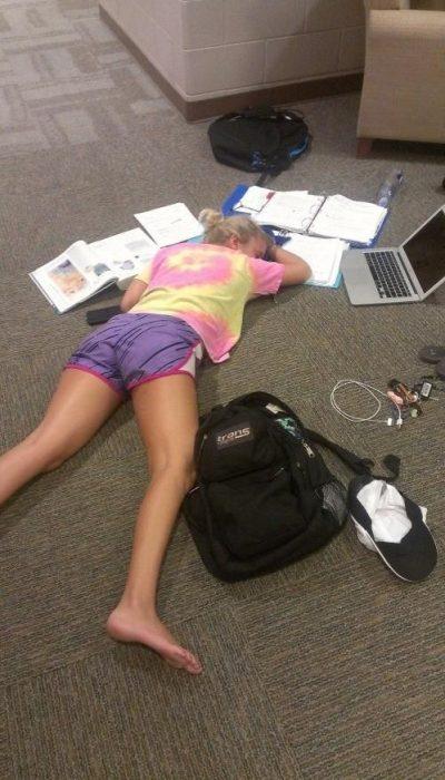 chica acostada en el suelo entre papeles y computadora