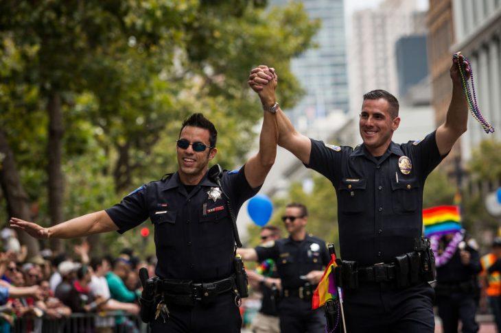 policías hombres tomados de la mano participan desfile gay