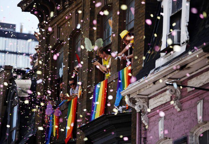 personas avientan confeti desde su ventana durante desfile gay
