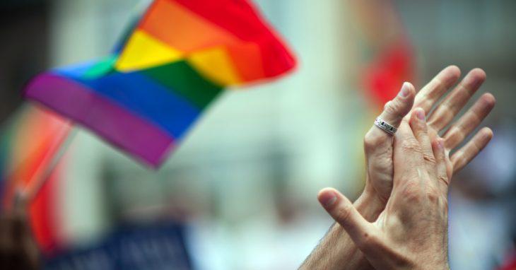 manos entrelazadas con bandera gay al fondo
