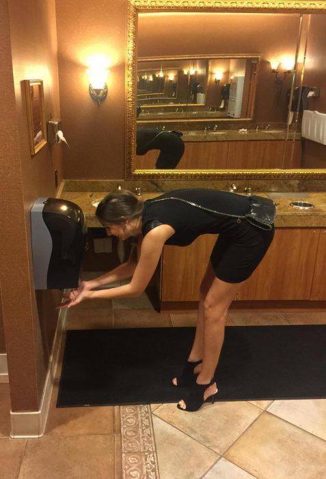mujer muy alta se agacha en baño público