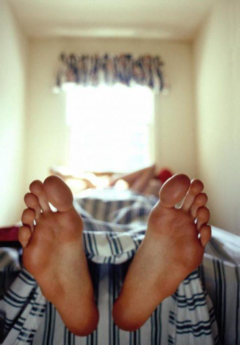 pies que salen de una cama
