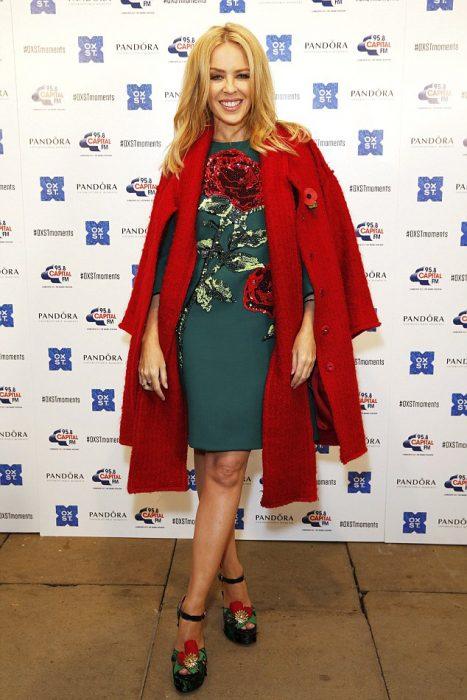 Kylie Minogue usando un vestido en color verde, con un saco en color rojo durante una alfombra roja
