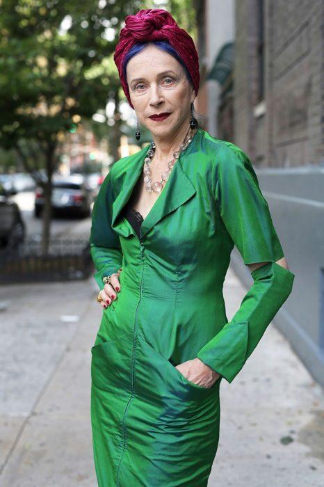 Mujer de más de 30 años vistiendo un traje en color verde y una mascada en color rojo