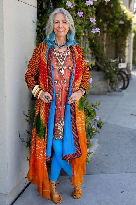 Mujer de la tercera edad usando un vestido de colores con un saco de colores y el cabello azul