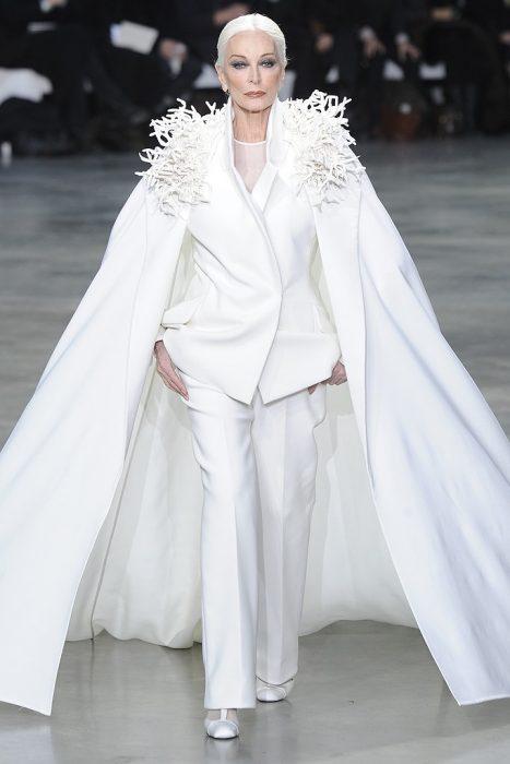 Carmen Dell'Orefice desfilando en una pasarela de modas minentras usa un traje sastre en color blanco con capa