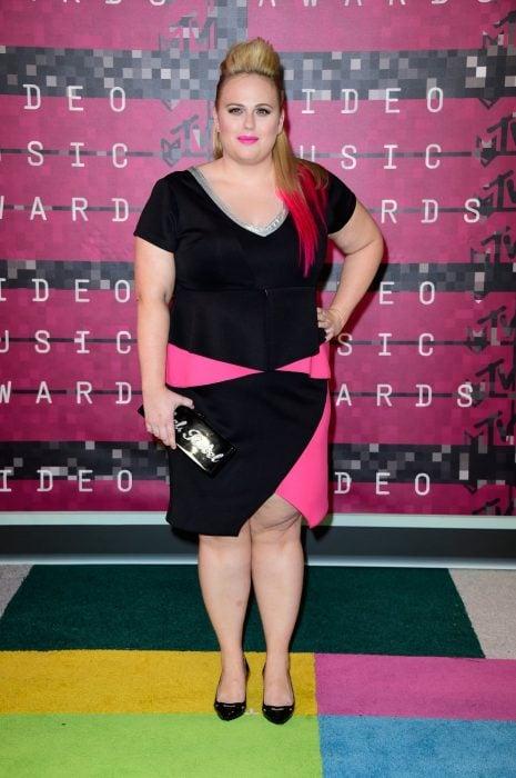 Rebel Wilson usando un vestido en color negro con rosa durante una entrega de premios