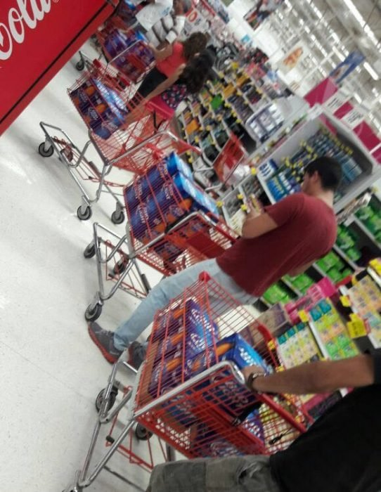 chicos en fila de supermercado con cartones de cerveza
