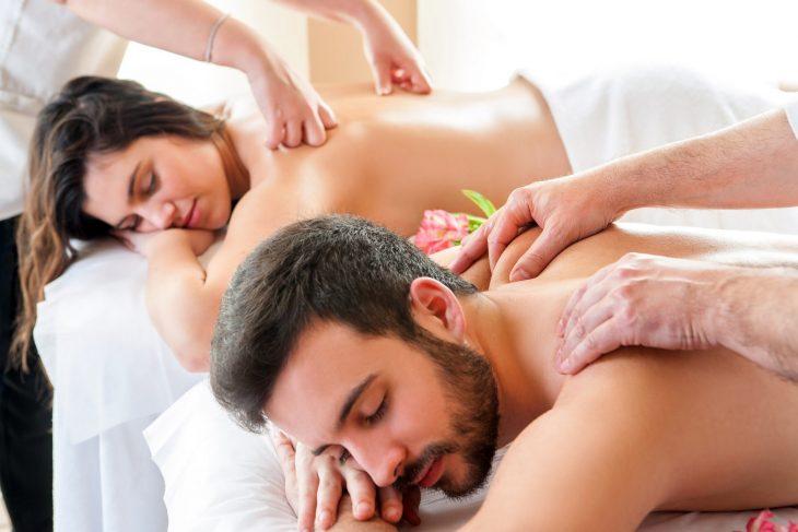 hombre y mujer acostados en camas mientras reciben masaje