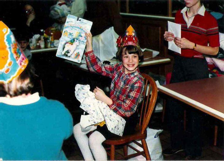 niña sentada en silla con juguete en la mano y gorro de cumpleaños