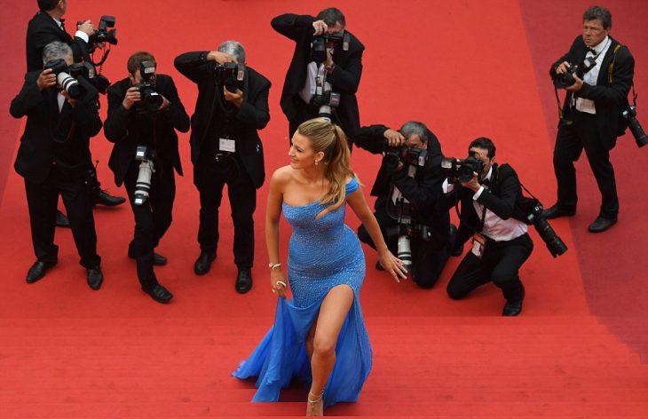 mujer subiendo las escaleras con vestido azul y fotógrafos atrás