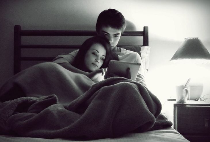 hombre y mujer acostados en una cama viendo una pantalla