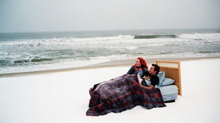 hombre en la cama con mujer de cabello rojo en medio del mar y nieve