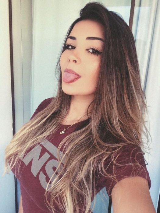 mujer moreja de cabello largo saca la lengua