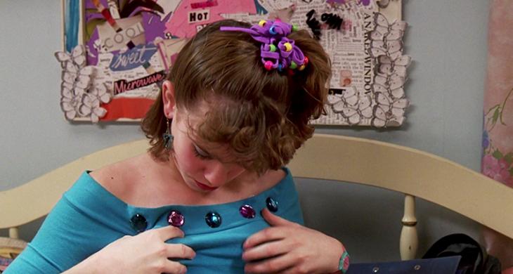 chica adolescente tocando sus pechos con blusa azul