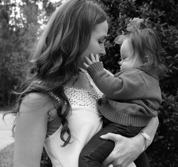 Madre con hija en sus brazos bebé con sindrome de Down