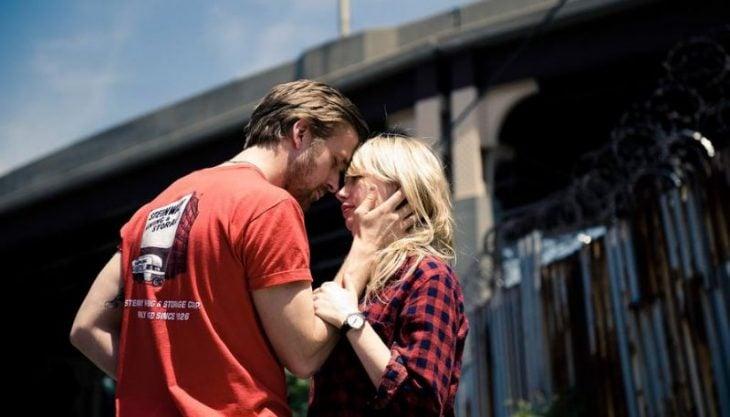 Pareja de novios mirándose a los ojos frente a un puente, escena película Blue Valentine, Cindy, Dean, Michelle Williams, Ryan Gosling