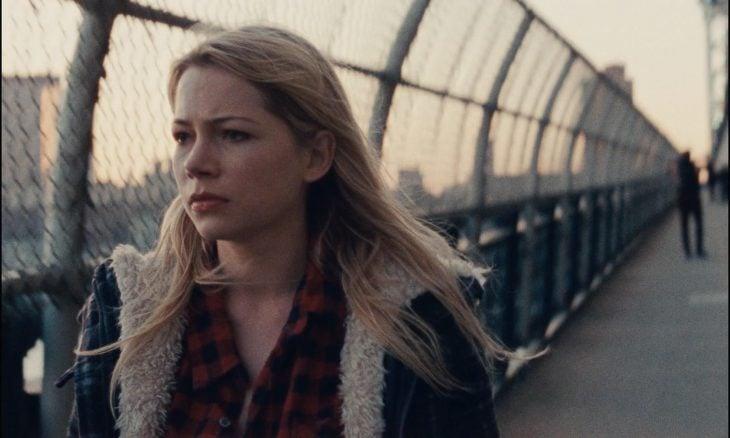 Chica caminando sobre un puente con rejillas alrededor, escena película Blue Valentine, Cindy, Michelle Williams