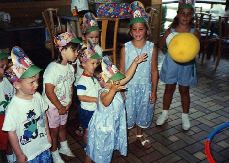 niños en restaurante con gorros de fiesta