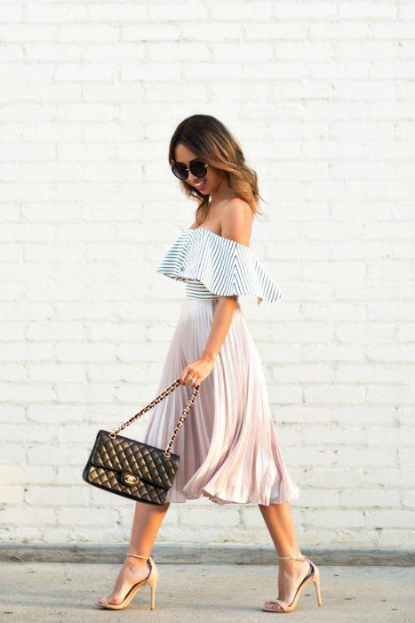 Chica usando una blusa sin hombros y una falda en color rosa