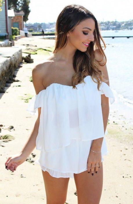 Chica usando una blusa sin hombros mientras está en la playa