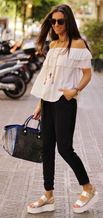 Chica usando una blusa sin hombros y pantalón en color negro