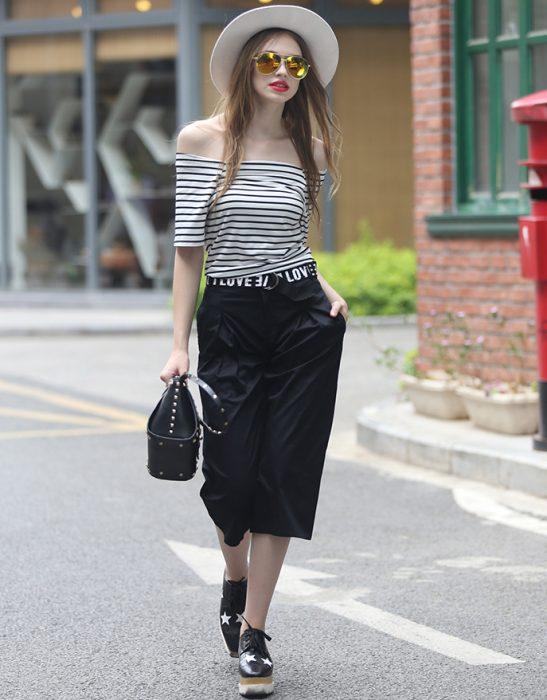 Chica usando una blusa sin hombros y pantalón capri en color negro