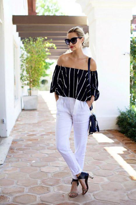 Chica usando una blusa sin hombros y un pantalón blanco