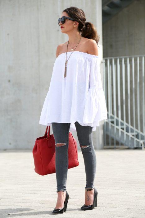 Chica usando una blusa sin hombros y unos leggins en color girs mientras sostiene un bolso en color rojo
