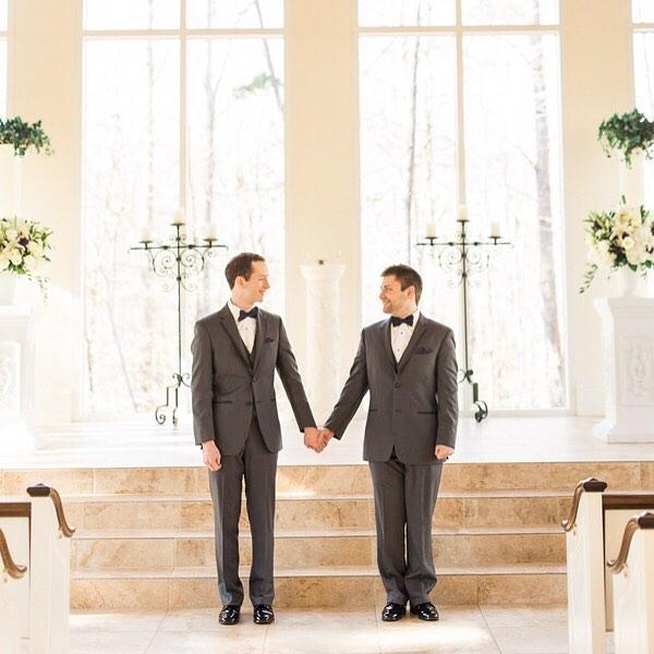 Pareja gay tomada de la mano frente al altar