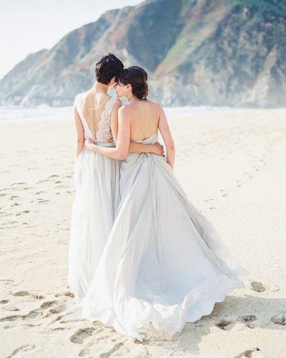 Chicas recién casadas caminando a la orilla de la playa