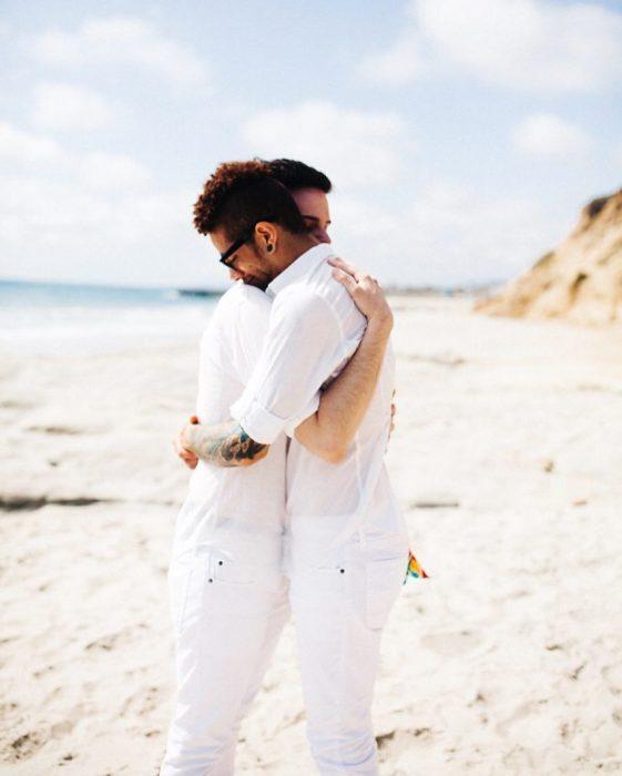 Pareja de chicos gays abrazados en la playa
