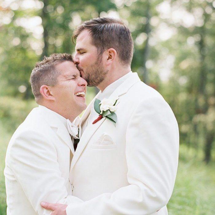 Pareja gay besándose la frente el día de su boda