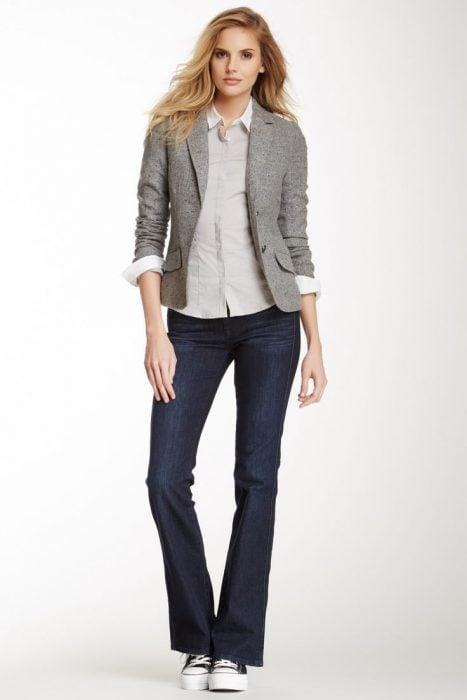 chica con jeans oscuros y blazer gris