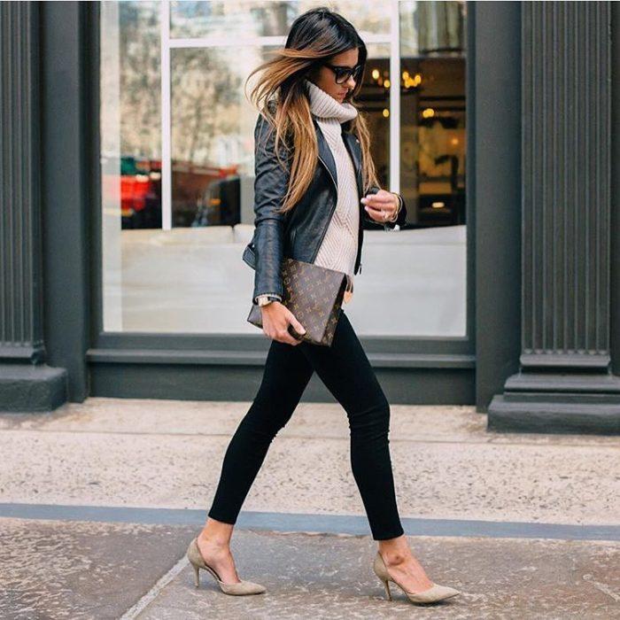 chica con jeans oscuros, tacones y cartera