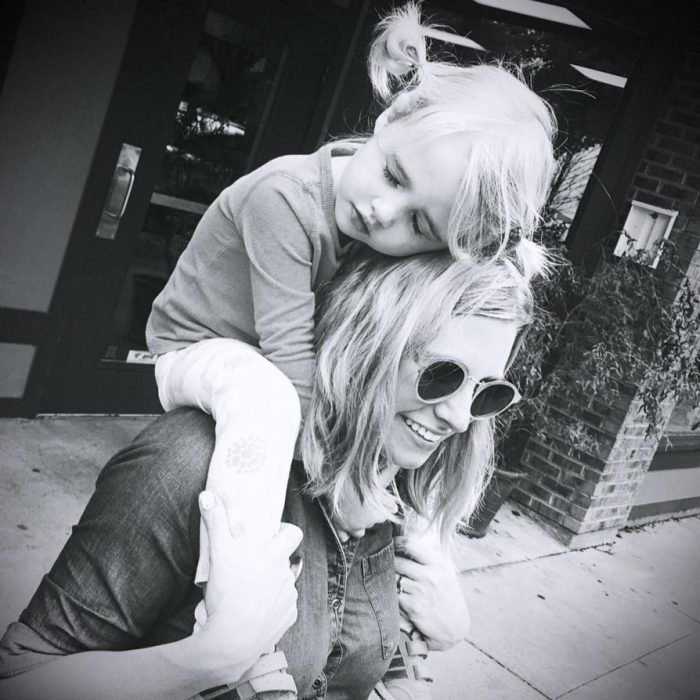 Niña sobre los brazos de su madre