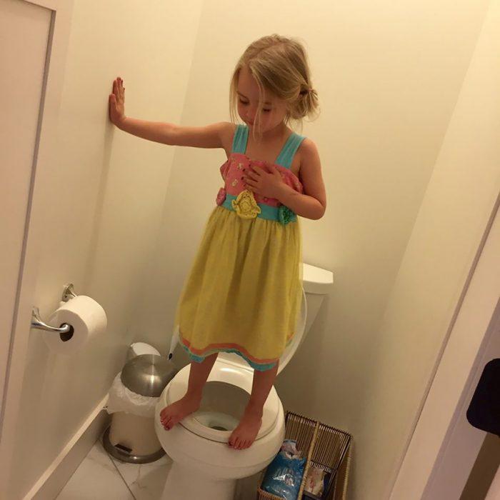 Niña sobre la tapa de un inodoro escondida en un baño