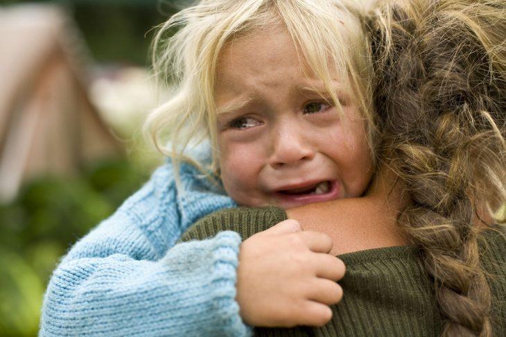 Niña llorando mientras abraza a su madre