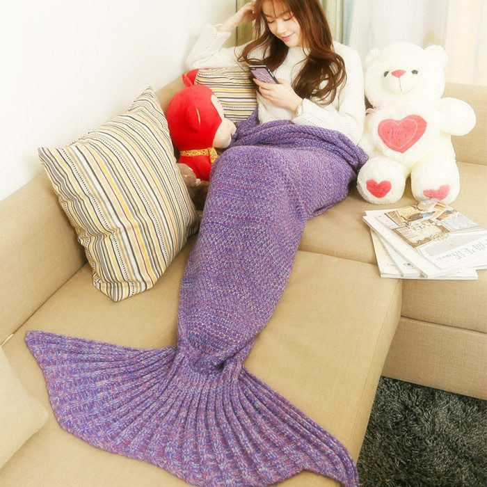 Chica recostada en un sofá viendo su celular mientras tiene las piernas cubiertas con una frazada cola de sirena