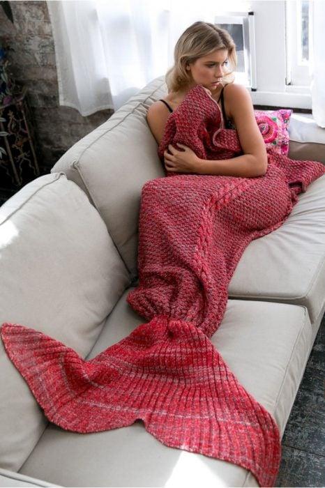 Chica recostada en un sofá mientras tiene las piernas cubiertas por una frazada cola de sirena