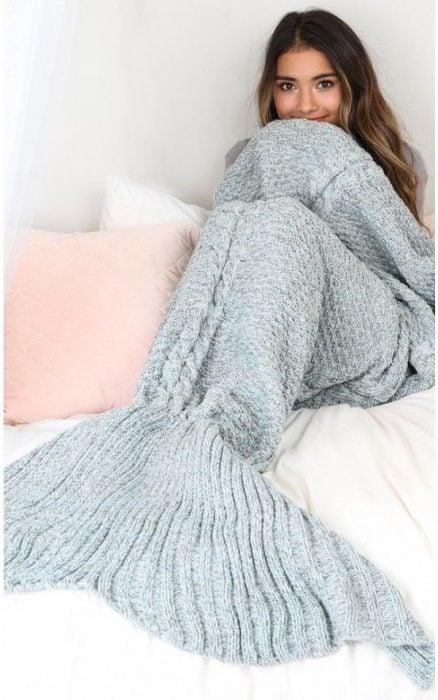 Chica recostada en una cama con los pies cubiertos por una frazada cola de pez