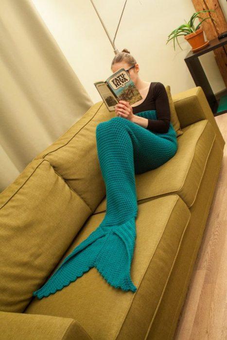 Chica sentada en un sofá leyendo mientras tiene las piernas cubiertas por una frazada cola de sirena