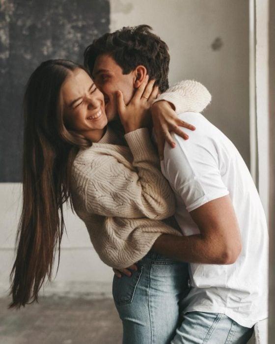 Pareja de novios abrazándose y riendo