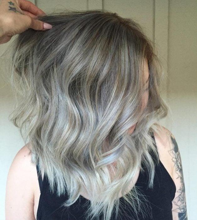 Chica usando un corte de cabello long bob en capas con un tinte en tonos gris