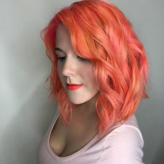 Chica usando un corte de cabello long bob con un tinte en color naranja
