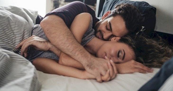 Pareja abrazada de cucharita en la cama